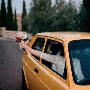 novia en el coche con ramo