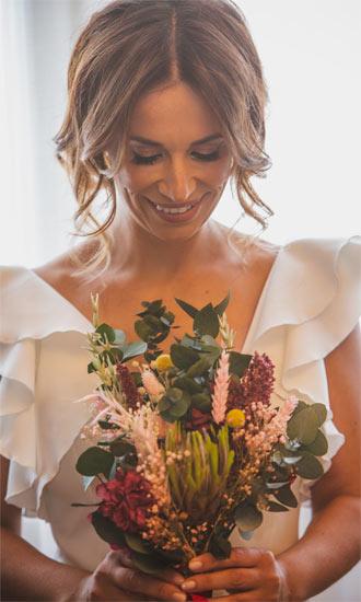 novia mirando a ramo de flores preservado