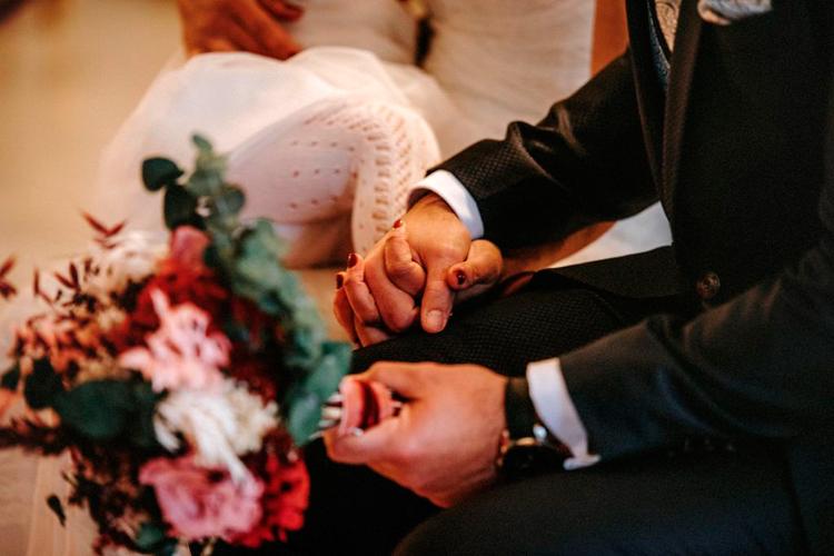 ramo de novia conn flores preservadas y manos de los novios