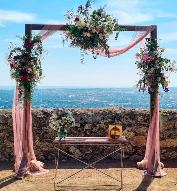 arco de flores preservadas junto al mar